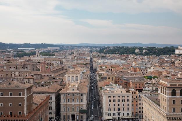 이탈리아 로마 - 2018년 6월 21일: 로마의 비토리아노라고도 알려진 비토리오 에마누엘레 2세 기념비에서 베네치아 광장과 도시의 탁 트인 전망. 푸른 하늘이 있는 교통 자동차와 여름날