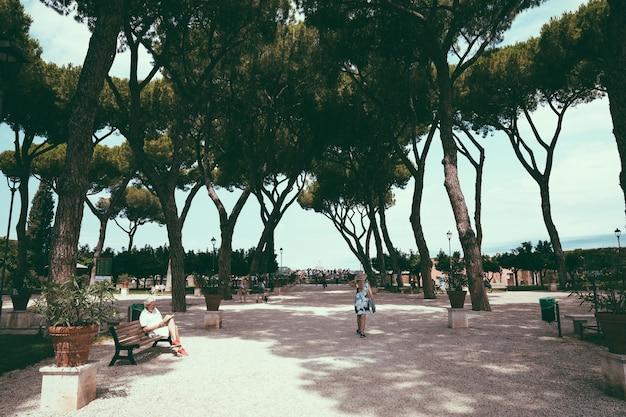 Рим, италия - 23 июня 2018: панорамный вид на апельсиновый сад (джардино дельи аранчи) на холме авентино. люди гуляют и отдыхают в национальном парке рима. летний день и голубое небо