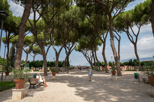 이탈리아 로마 - 2018년 6월 23일: aventino hill에 있는 orange garden(giardino degli aranci)의 탁 트인 전망. 사람들은 로마의 국립 공원에서 걷고 휴식을 취합니다. 여름날과 푸른 하늘