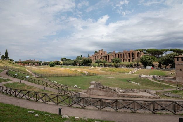 로마, 이탈리아 - 2018년 6월 23일: 고대 로마의 팔라티노 언덕에 있는 아폴로 팔라티누스 신전의 탁 트인 전망과 서커스 막시무스(circo massimo)는 고대 로마 경주 경기장이자 대규모 엔터테인먼트입니다.