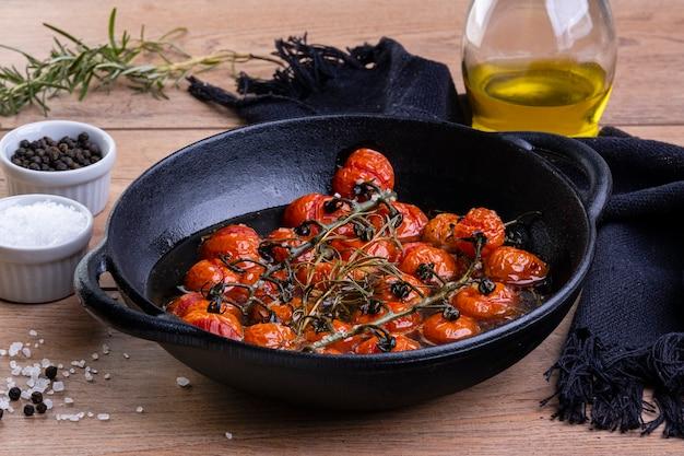 木製のテーブルにコンフィトマトとロンキャセロール。