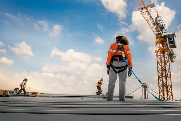 Строитель, носящий ремни безопасности и линии безопасности, работающие на металлической промышленности roo