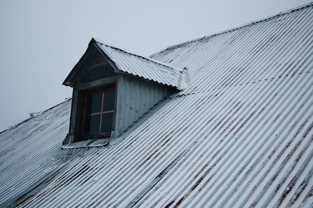 Roof of the building covered in snow against the cloudy sky