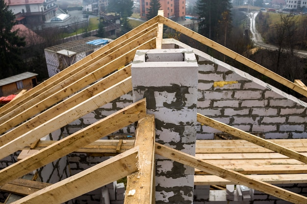Roof frame of rough wooden lumber beams and chimney made of foam insulation blocks
