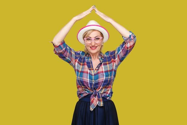 頭の上の屋根のジェスチャー。帽子が立っている、頭の上に手をつないで、歯を見せる笑顔で見ているカジュアルなスタイルの幸せでモダンなスタイリッシュな成熟した女性の肖像画。黄色の背景に分離されたスタジオショット。