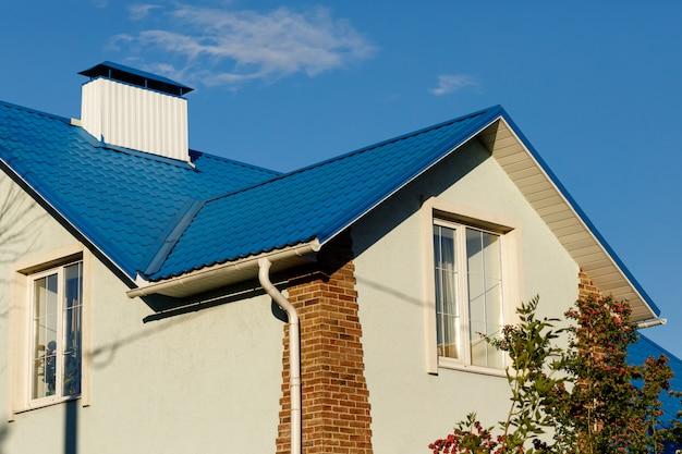 A roof of a house or cottage made of blue metal tiles with drains, slopes and chimney against the blue sky.