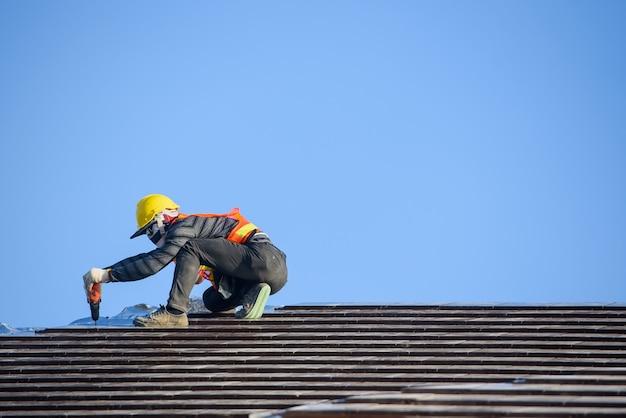 Монтажник крыши устанавливает крышу дома, то есть керамическую черепицу на строительной площадке.