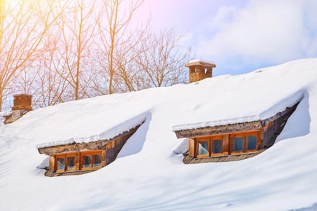 雪に覆われた窓のある低層の木造村の家の屋根。冬