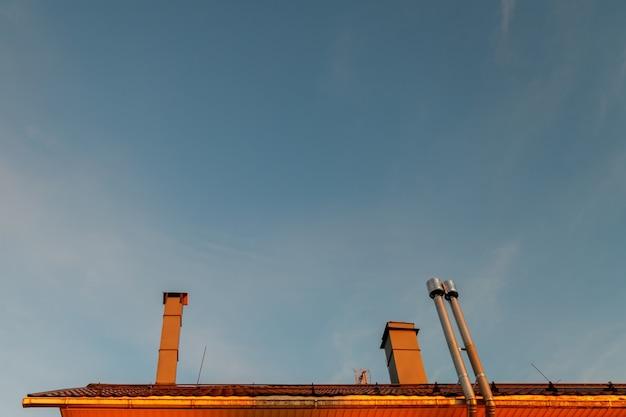 맑고 푸른 하늘을 굴뚝이 있는 집 지붕. 철제 굴뚝이 있는 현대적인 금속 지붕