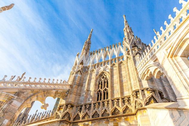 ゴシック様式の尖塔と白い大理石の彫像があるミラノ大聖堂ドゥオーモディミラノの屋根