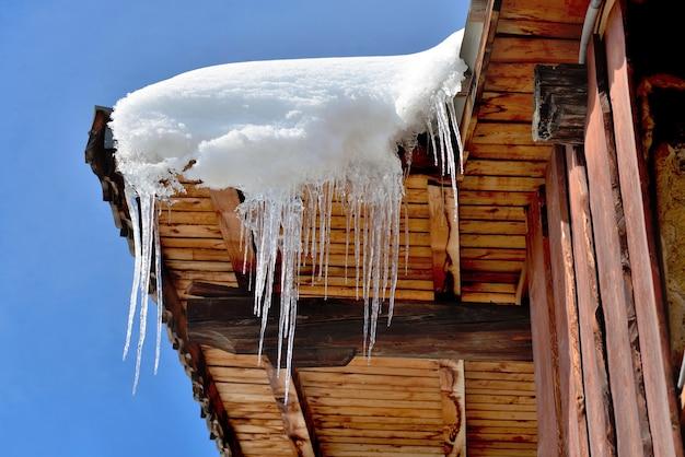 Крыша деревянного дома в альпийской деревне покрыта снегом и сосульками