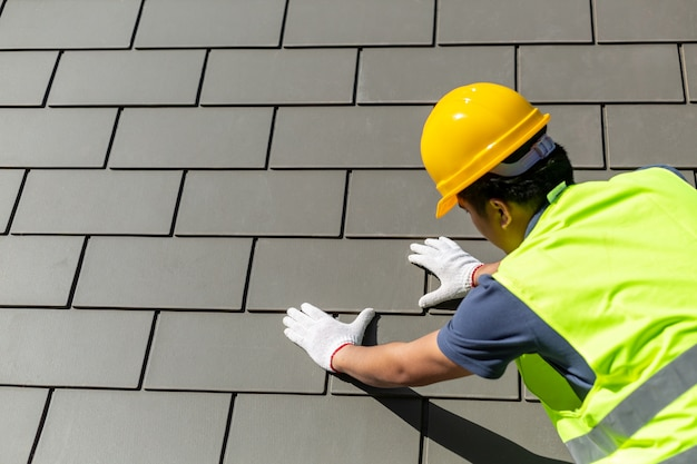 Roof repair, worker with white gloves replacing gray tiles or shingles on house with blue