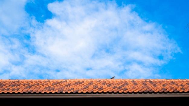 하늘 배경에 옥상입니다. 갈색 점토 지붕 타일을 닫습니다. 빨간색 오래 된 더러운 지붕입니다. 오래 된 지붕 타일입니다. 구시가지의 푸른 여름 하늘이 있는 전통적인 붉은 지중해 지붕의 클로즈업 공중 전망