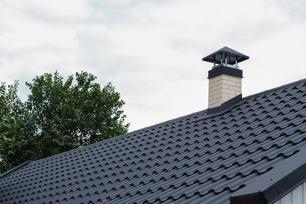 어두운 금속 타일과 굴뚝 금속 지붕 포진이 있는 지붕