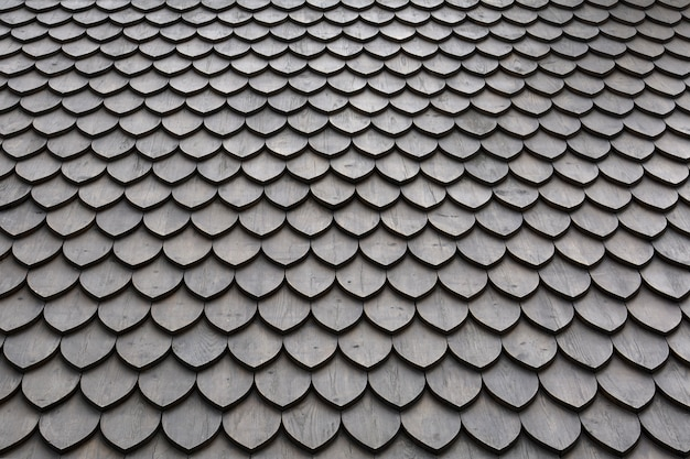 Roof with wooden petal tile texture, laid in smooth rows.