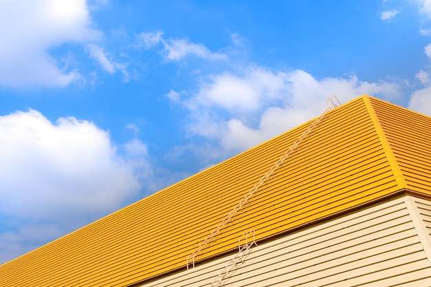 Roof on a yellow background of blue sky.