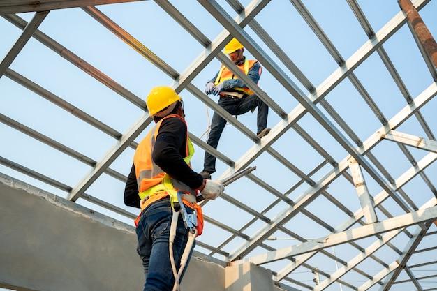 屋根葺き職人の労働者は、屋根の上の新しい屋根に金属板を取り付けます。未完成の屋根の建設。