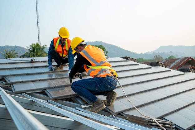 Roofer builder worker installing ceramic roof on top of the new roof at construction site.