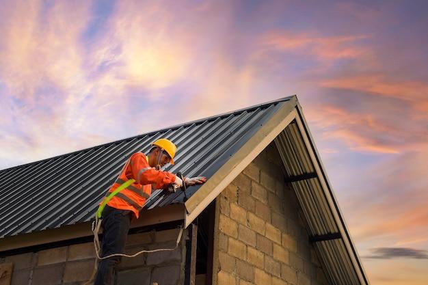 Roofer 건설 노동자는 새로운 지붕, 루핑 도구, 금속 시트가있는 새 지붕에 사용되는 전기 드릴을 설치합니다.