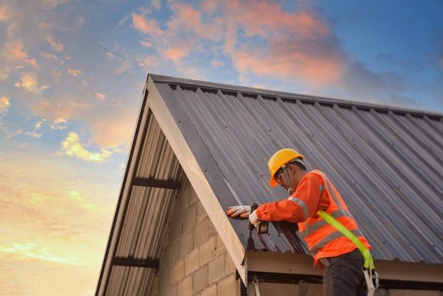 屋根葺き職人の建設労働者は、新しい屋根、屋根ふき用具、金属板を備えた新しい屋根に使用される電気ドリルを取り付けます。