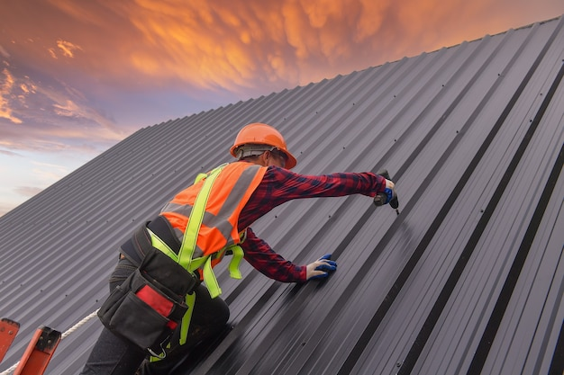 Кровельщик строитель устанавливает новую крышу кровельные инструменты электродрель используется на новых крышах