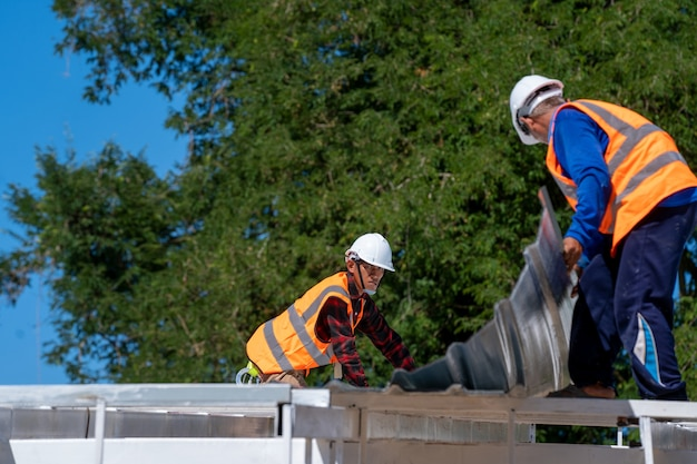 The roofer technicians work and installing new roof structure on top roof of house,metal roof,fasteners corrugated sheets.