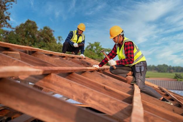屋根葺き職人、建設現場の屋根構造に取り組んでいる2人の屋根葺き職人、チームワーク建設コンセプト。