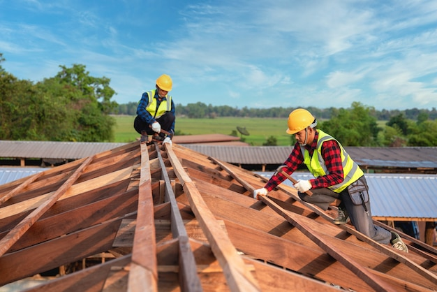 Roofer, two worker roofer builder working on roof structure on construction site, teamwork construction concept.