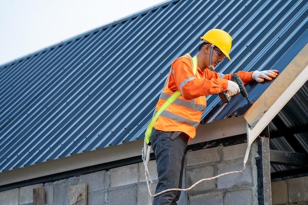 Кровельщик использует пневматический или пневматический пистолет для гвоздей и устанавливает металлический лист на новую крышу.