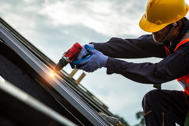 Кровельщик в защитной униформе и перчатках, строитель устанавливает новую крышу, кровельные инструменты, электродрель используется на новых крышах с металлическим листом.