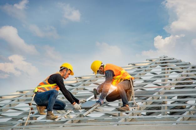保護作業服と手袋の屋根葺き職人、空気または空気圧式の釘打ち機を使用し、新しい屋根の上にコンクリート屋根瓦を取り付ける、建設中の住宅建築の概念。