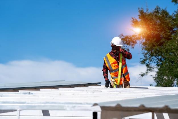 Кровельщик в защитной униформе и перчатках работает, устанавливая металлический лист поверх новой крыши на строительной площадке.