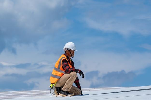 Кровельщик в защитной униформе и перчатках работает, устанавливая металлический лист поверх новой крыши на строительной площадке. Premium Фотографии