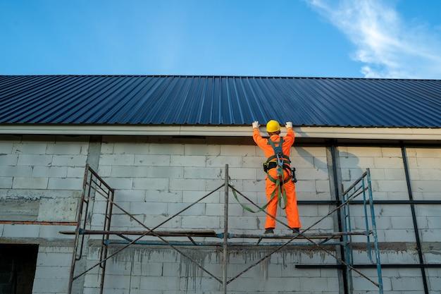 防護服と安全ライン作業の屋根葺き職人が建設現場に新しい屋根を取り付けます。