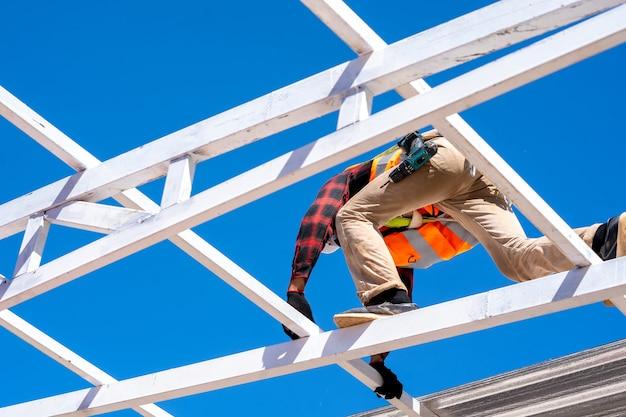 Кровельщик в защитной униформе, устанавливающей металлическую крышу поверх новой крыши, концепция строящегося жилого дома, работа на высоте.
