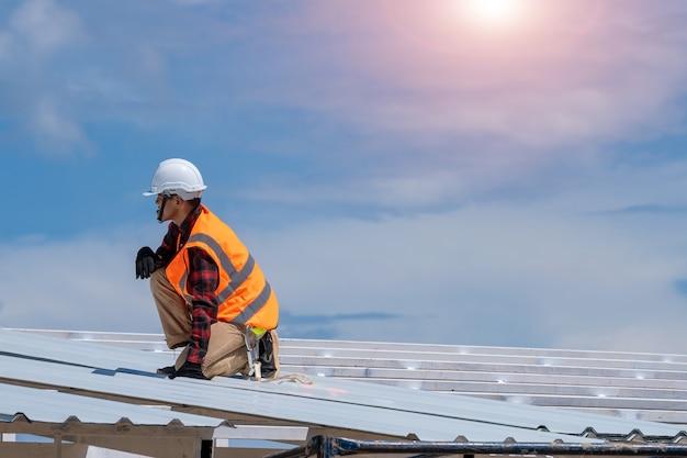Кровельщик в защитной униформе, устанавливающей металлическую крышу поверх новой крыши, концепция строящегося жилого дома.