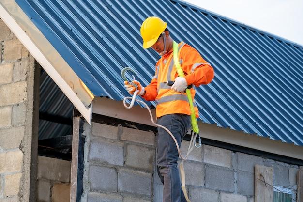 Кровельщик в специальной защитной установке новой крыши на верхней крыше.