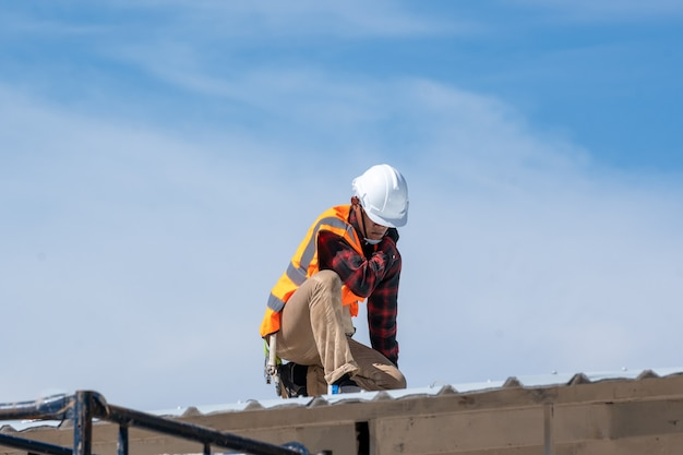 Roofer worker in protective uniform wear and gloves working installing metal sheet on top of the new roof at construction site.