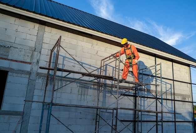 Roofer worker in protective uniform wear and safety line working install new roof at construction site.