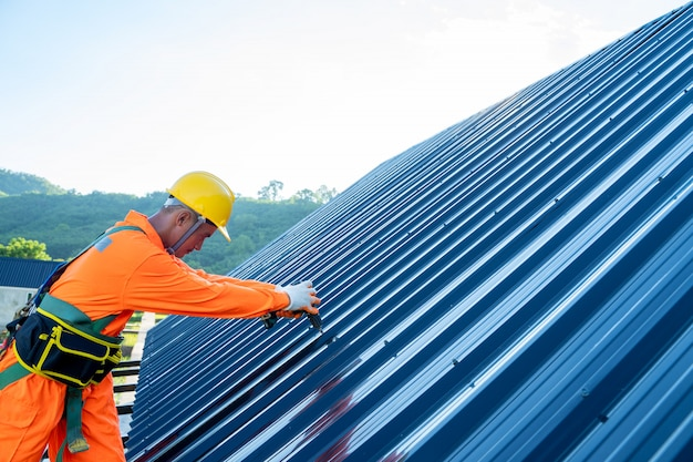 Roofer worker in special protective workwear use electric drill