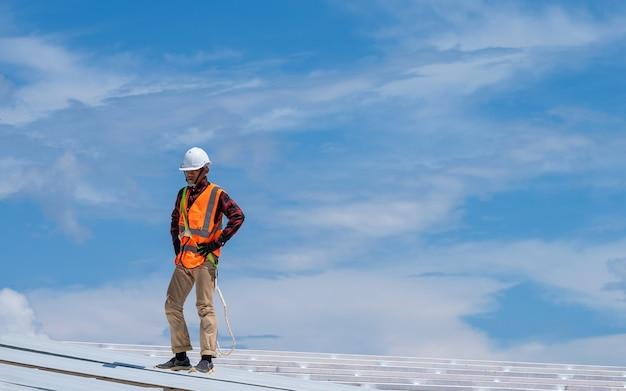 Кровельщик, работающий в защитных перчатках, строительный рабочий в ремнях безопасности, работающих на высоком уровне на строительной площадке, устанавливает новую крышу, металлическую крышу.