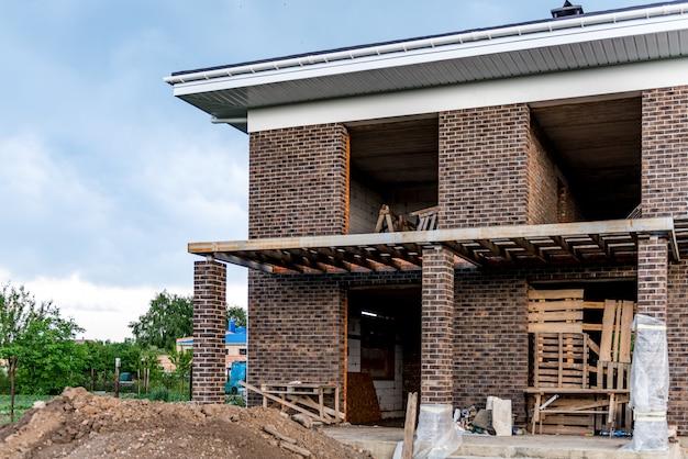 屋根の建設とモジュール式煙突のある新しいれんが造りの家の建設 Premium写真