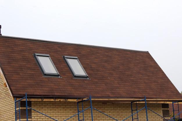 지붕 공사 및 채광창이 있는 새 집 짓기, 굴뚝이 있는 새 벽돌 집. 현대 지붕 채광창. 다락방 채광창 홈 디자인. 지붕 공사. 점토 기와.