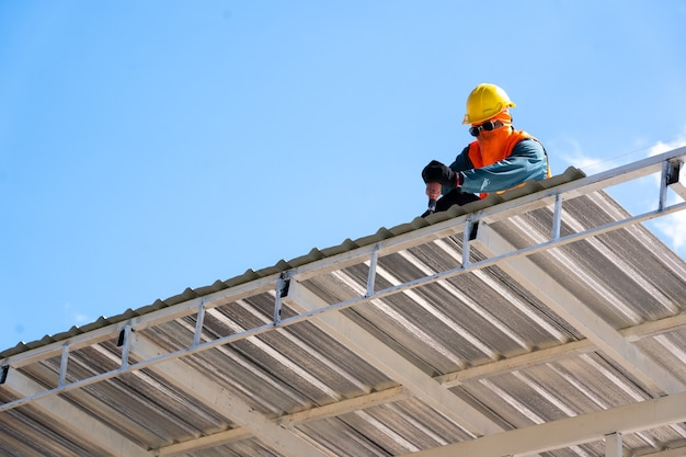Roofing,construction workers wearing safety harness checking and installation assembly of new roof,roofing tools.