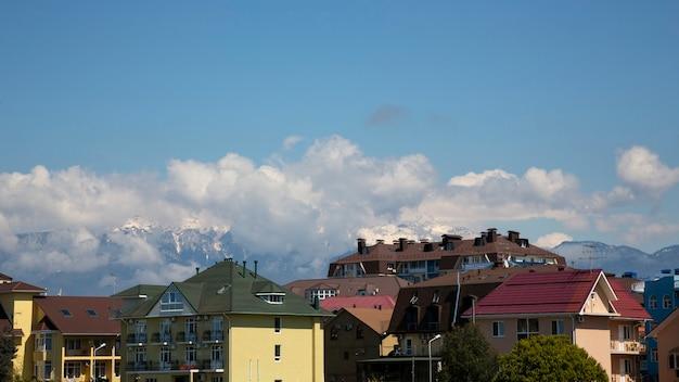산과 하늘을 배경으로 한 집들의 지붕. 산악 지역의 작은 마을