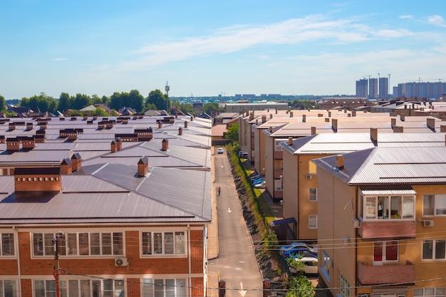 Крыши домов в спальном районе небольшого городка. коттеджный поселок в городе в солнечный летний день.