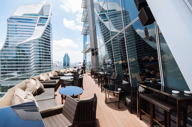 Rooftop hotel restaurant with modern high rise buildings in the background.