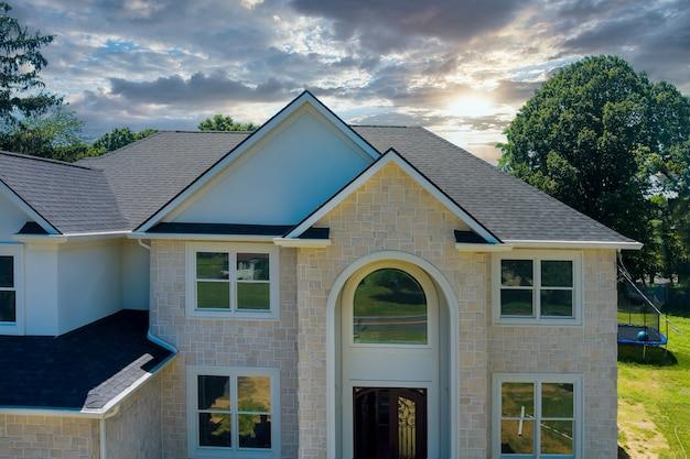 アスファルトが複数のルーフラインを屋根板で覆っている新築住宅の屋上