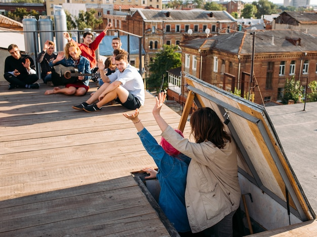 Rooftop party newcomers. young people wave hello to their friends. youth leisure and pastime. friendship and carefree life