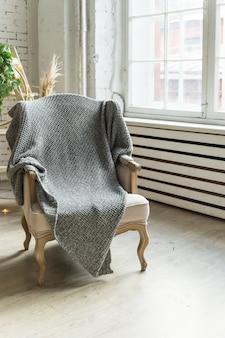 大きな窓の近くの灰色の毛布で木の床にクラシックな椅子。信頼性が高く快適なroom.countryスタイルの椅子。ビンテージスタイルのベッドルームのインテリアの椅子。スタイリッシュな部屋のインテリア
